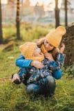 Mamman i en gul hatt kramar hennes son i en gul hatt arkivbild