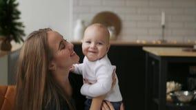 Mamman kramar behandla som ett barn, och barnet ler se hans älskade moder Tillsammans ställning i det vita köket på jul stock video