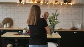 Mamman kramar behandla som ett barn, och barnet ler se hans älskade moder Tillsammans ställning i det vita köket på jul lager videofilmer