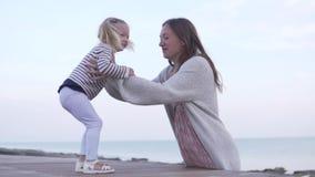 Mamman kramar den lilla dottern Behandla som ett barn hopp till mamman i hennes armar och kysser henne stock video