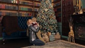 Mamman kramar försiktigt hennes lilla son nära julgranen lager videofilmer