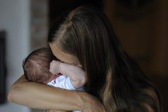 Mamman kramar henne för att behandla som ett barn royaltyfria foton