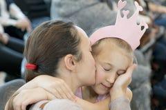 Mamman kysser försiktigt hennes dotter Royaltyfri Bild
