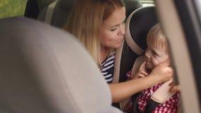 Mamman kysser och kramar hennes son i bilen i bilsäte lager videofilmer