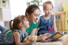 Mamman läser berättelse till hennes lilla döttrar royaltyfria bilder