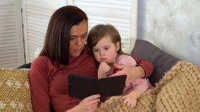 Mamman läser hans lilla dotter en saga stock video