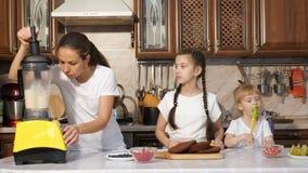 Mamman lagar mat kräm för kaka genom att använda blandaren med hennes två döttrar arkivfilmer