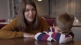 Mamman lugnar den lilla sonen som kränktes av hennes sammanträde på en tabell i ett kafé lager videofilmer