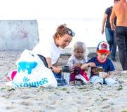 Mamman matar barn på stranden arkivfoto