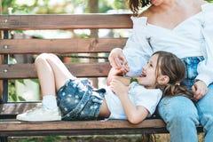Mamman matar hennes lilla dotter som glass i parkerar arkivbilder