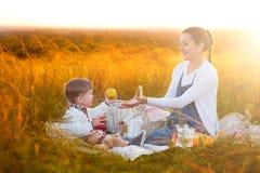 Mamman matar hennes son på en picknick Moder och barnson i solig nedgångdag Lycklig familj och sunt ätabegrepp arkivbilder