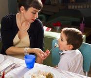 Mamman matar hennes son på tacksägelsekalkon Royaltyfria Bilder