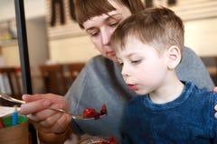 Mamman matar sonen med sallad av rödbeta fotografering för bildbyråer