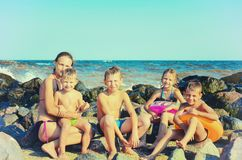 Mamman med barn p? havet p? havet p? stranden, vattnet sl?r p? stenarna Tonat tappningfoto royaltyfri foto