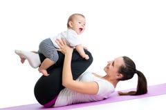 Mamman med barnet gör gymnastiska och konditionövningar royaltyfri foto