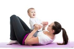 Mamman med behandla som ett barn gör gymnastik, och kondition övar Arkivbild