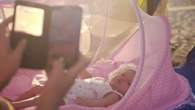 Mamman med den mobila tagande bilden av behandla som ett barn i den utomhus- babyliften stock video