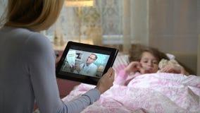 Mamman med den sjuka dottern får lite en doktors konsultation genom att använda video pratstund hemma arkivfilmer