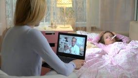 Mamman med den sjuka dottern får lite en doktors konsultation genom att använda video pratstund hemma stock video