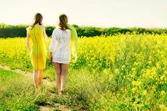 Mamman med dottern eller två systrar eller flickvänner i klänningar går mot bakgrunden av ett gult fält Baksida-sikt Royaltyfri Bild