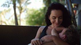 Mamman med ett barn utomhus och att amma honom och att ge bröstet mjölkar till ett barn som invaggar lilla barnet