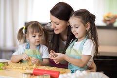 Mamman med hennes 2 och 5 år gamla döttrar lagar mat i köket till moderdagen royaltyfria foton