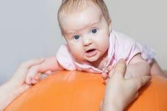 Mamman med lyckligt behandla som ett barn göra övningar på den gymnastiska bollen Royaltyfri Fotografi
