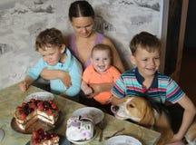 Mamman med tre ungar och en beagle på tabellen i förväntan av ett bär bakar ihop arkivbild