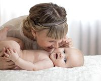 Mamman och behandla som ett barn att spela i soligt sovrum Moder och litet barn som hemma kopplar av familjgyckel som tillsammans Royaltyfria Bilder