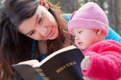 Mamman och behandla som ett barn den läs- bibeln för dottern Royaltyfri Foto