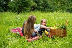 Mamman och behandla som ett barn flickan i natur Fotografering för Bildbyråer