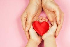 Mamman och behandla som ett barn händer med hjärta Arkivfoto