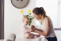 Mamman och behandla som ett barn i köket Kvinnan ska mata behandla som ett barn med behandla som ett barn mat Arkivfoto