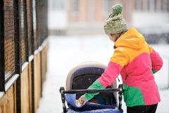 Mamman och behandla som ett barn i sittvagn går på, snöig vinterväder Snöfall häftig snöstorm som är utomhus- Royaltyfria Bilder