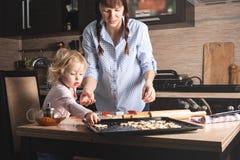 Mamman och behandla som ett barn kopplas in, i att baka kakor hemma i hennes kök Inte arrangerat fragment från verkliga livet arkivbilder