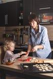 Mamman och behandla som ett barn kopplas in, i att baka kakor hemma i hennes kök Inte arrangerat fragment från verkliga livet arkivfoton