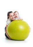Mamman och behandla som ett barn med den gymnastiska bollen Royaltyfri Foto