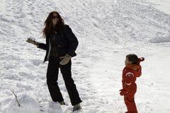 Mamman och behandla som ett barn med rött skidar dräkten i snön Royaltyfri Foto