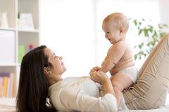 Mamman och behandla som ett barn pojken i blöjan som spelar i soligt rum Moder och liten unge som hemma kopplar av familjgyckel s Royaltyfria Bilder