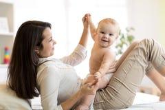 Mamman och behandla som ett barn pojken i blöjan som spelar i soligt rum Moder och liten unge som hemma kopplar av familjgyckel s Royaltyfri Foto