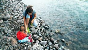 Mamman och behandla som ett barn sitter på flodbanken lager videofilmer