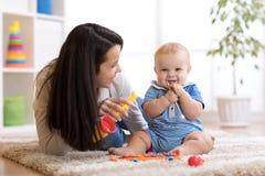 Mamman och behandla som ett barn spela musikaliska leksaker hemma Arkivfoton