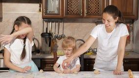 Mamman och döttrar kastar mjöl till varandra, medan laga mat i köket arkivfilmer