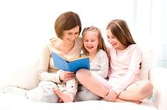 Mamman och döttrar som reaading barn` s, bokar royaltyfri fotografi