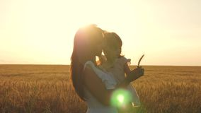 Mamman och den lilla dottern promenerar en landsväg i ett vetefält modern och att behandla som ett barn går i natur lycklig mom lager videofilmer