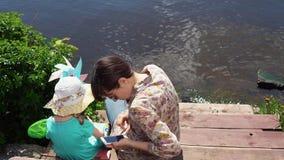 Mamman och den lilla dottern sitter på pir på sjön arkivfilmer
