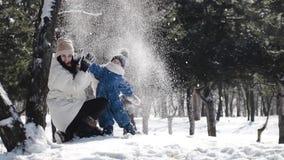 Mamman och den lilla sonen spelar kastar snöboll och kastar upp snö arkivfilmer