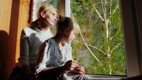 Mamman och dottern är 6 år gammalt sammanträde på fönsterbrädan som ut ser fönstret Utanför fönstret är våren, gör grön lager videofilmer