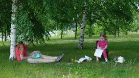 Mamman och dottern är förlovade i kreativitet parkerar in i skugga under träd stock video
