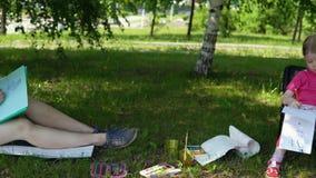 Mamman och dottern är förlovade i kreativitet parkerar in i skugga under träd arkivfilmer